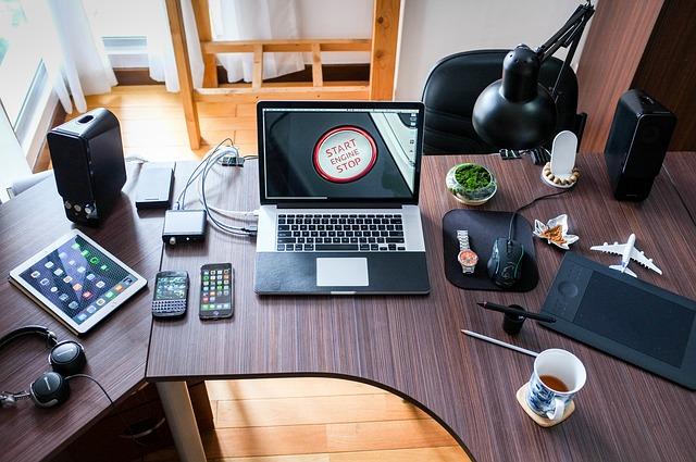 kancelář, psací stůl, notebook, mnoho různých věcí na stole, lampa, hrnek, mobil, tablet, vedle židle
